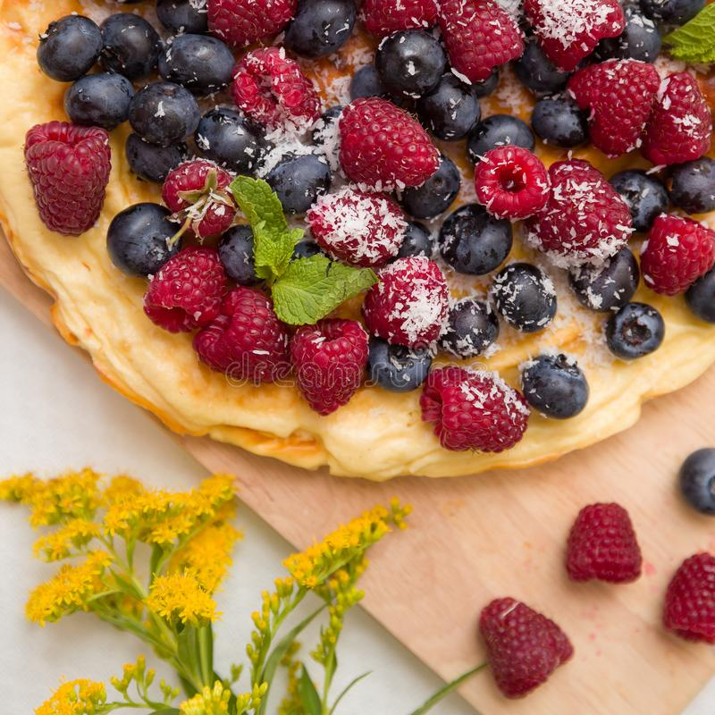 Fresh berries on the tart cake from above. Delicious homemade pie with organic raspberries and blueberries and flowers stock image