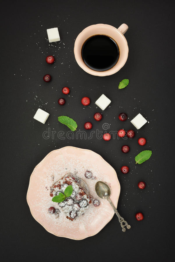 Fresh berries on tart cake, cup coffee, fresh cranberry and sugar cubes over black background. Top view. royalty free stock photos