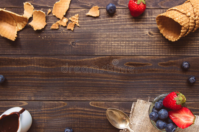 Fresh berries, waffle cone and chocolate sauce on the wooden background, top view. Ice-cream background with copy space stock photography