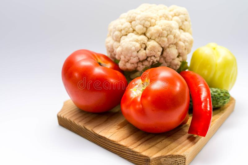 Fresh, bio,  garden growth vegetables on pine cutting board. Close up shot on gray background stock image