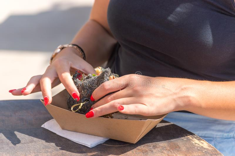 Fresh black grilled burger in woman`s hands. Street food festival royalty free stock images