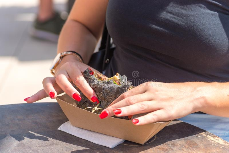 Fresh black grilled burger in woman`s hands. Street food festival royalty free stock image