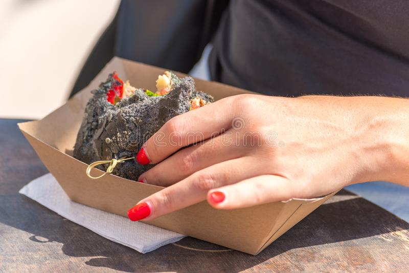 Fresh black grilled burger in woman`s hands. Street food festival stock photography