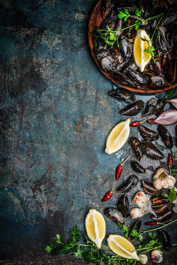 Fresh black mussels in wooden bowl with lemon and ingredients for cooking on dark rustic background, top view, borde royalty free stock photography