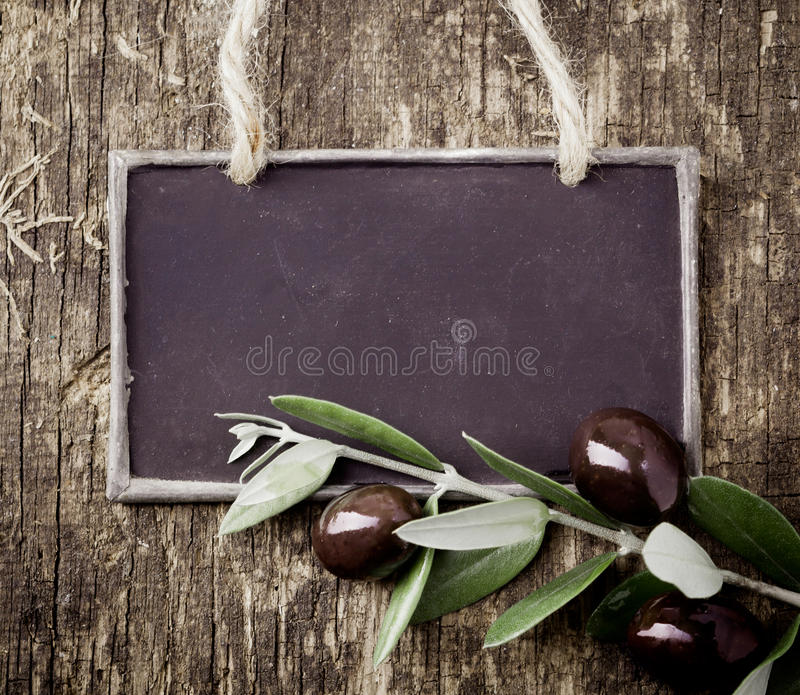 Fresh black olives and a blank slate royalty free stock photo
