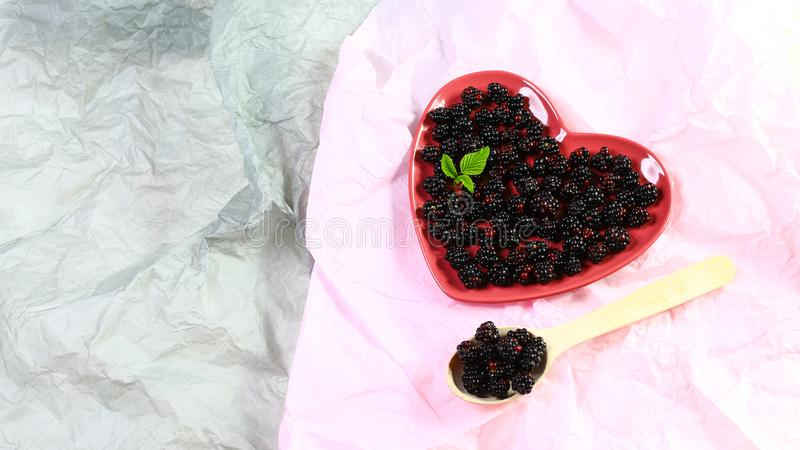 Fresh blackberries on a plate with blackberry leaves, on gray background, Authentic lifestyle image. top view, copy space royalty free stock image