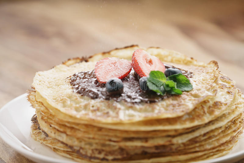 Fresh blinis or crepes with melted dark chocolate, berries and sugar powder. Shallow focus stock photos