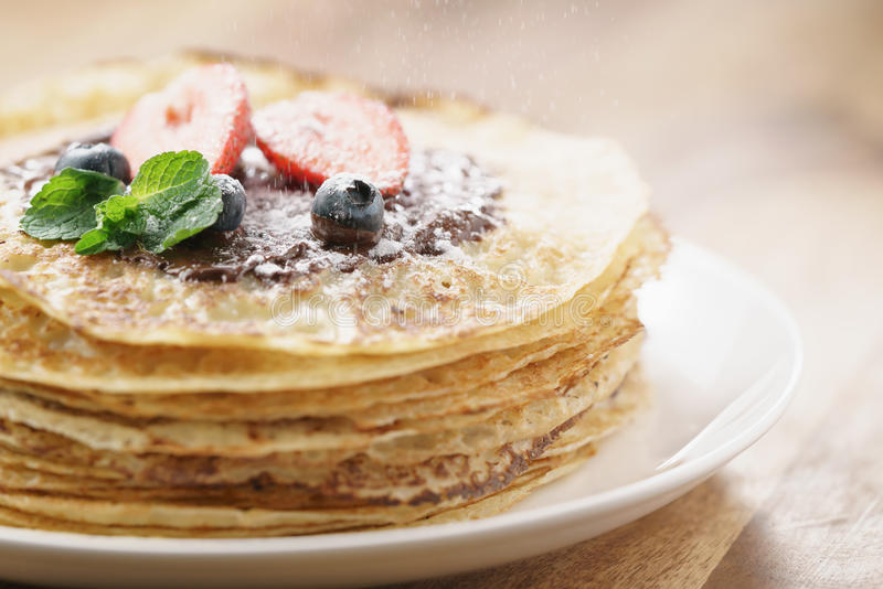 Fresh blinis or crepes with melted dark chocolate, berries and sugar powder. Shallow focus royalty free stock photos