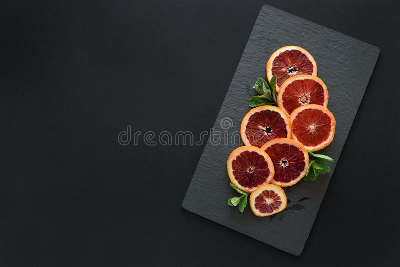 Fresh blood orange slices decorated mint leaves on dark slate background. Top view. Copy space.  royalty free stock photo