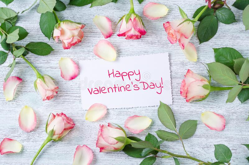 Fresh blossom rose flowers and petals with a white card and text happy valentine`s day on the vintage wooden background stock images