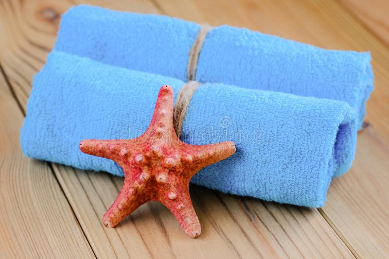 Rolled towels. Fresh blue rolled towels and a red starfish royalty free stock photo