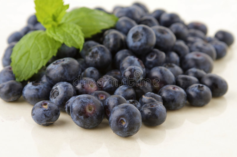 Fresh blueberries. On white kitchen table with mint leave stock photography