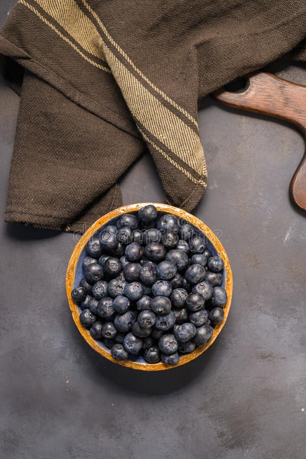 Fresh blueberries in ceramic bowl and brown cloth royalty free stock image