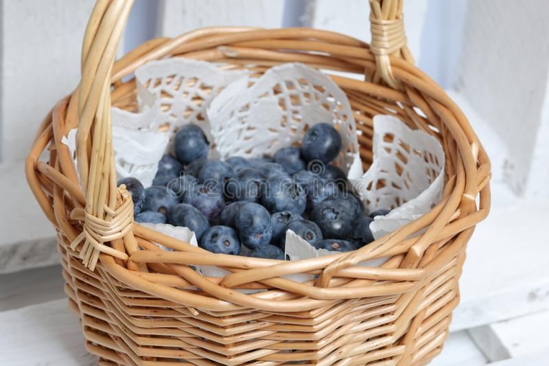 Fresh blueberries are collected in a wicker basket, laid with a paper napkin. It is in a box of white painted boards stock photography