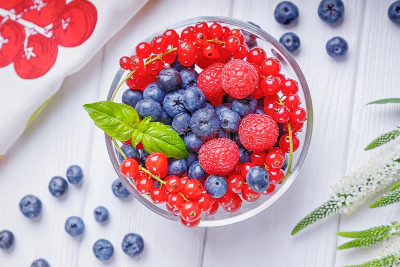 Blueberries, raspberries and red currant in a bowl on a white wooden background. Top view stock photos
