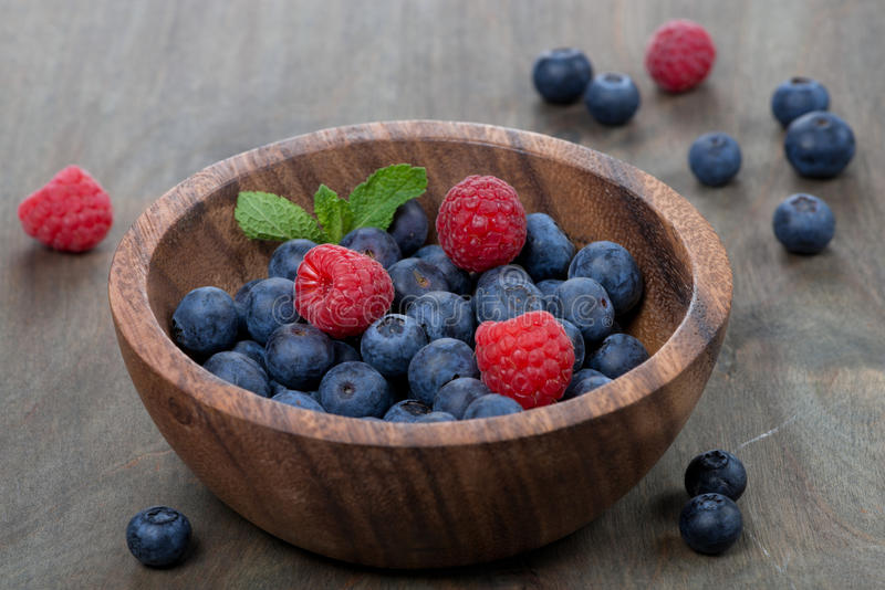 Fresh blueberries and raspberries in wooden bowl royalty free stock photography