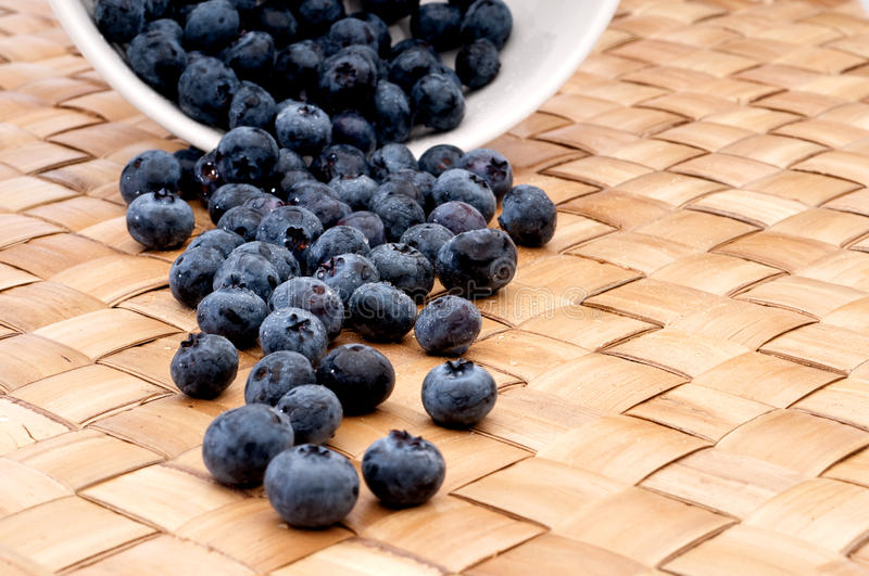 fresh blueberries spilling from a bowl stock images
