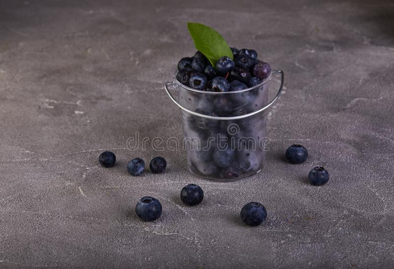 Fresh blueberries in a transparent bucket on a gray concrete royalty free stock photography