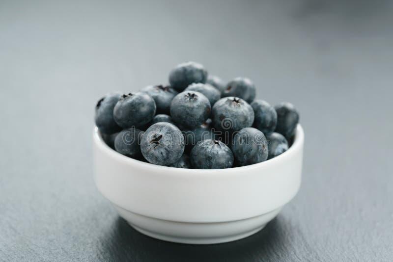 Fresh blueberries in white bowl on slate board stock photo