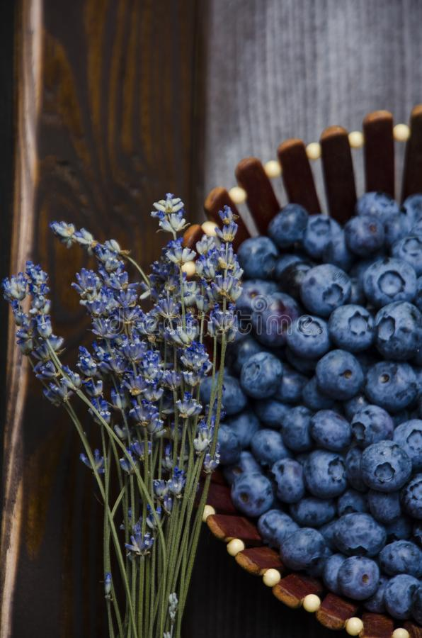 Fresh blueberries on a wooden board, dark background. Lavender. Vertical photo. Kiev, July 2019 stock photo