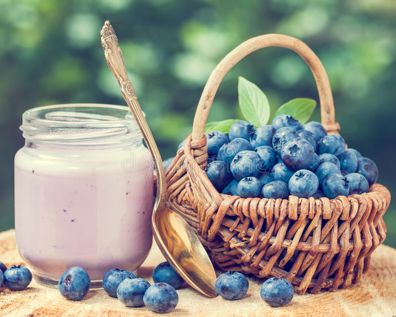 Fresh blueberries yogurt in jar and basket with bilberries. Fresh blueberries yogurt in glass jar and wicker basket with bilberries royalty free stock photos