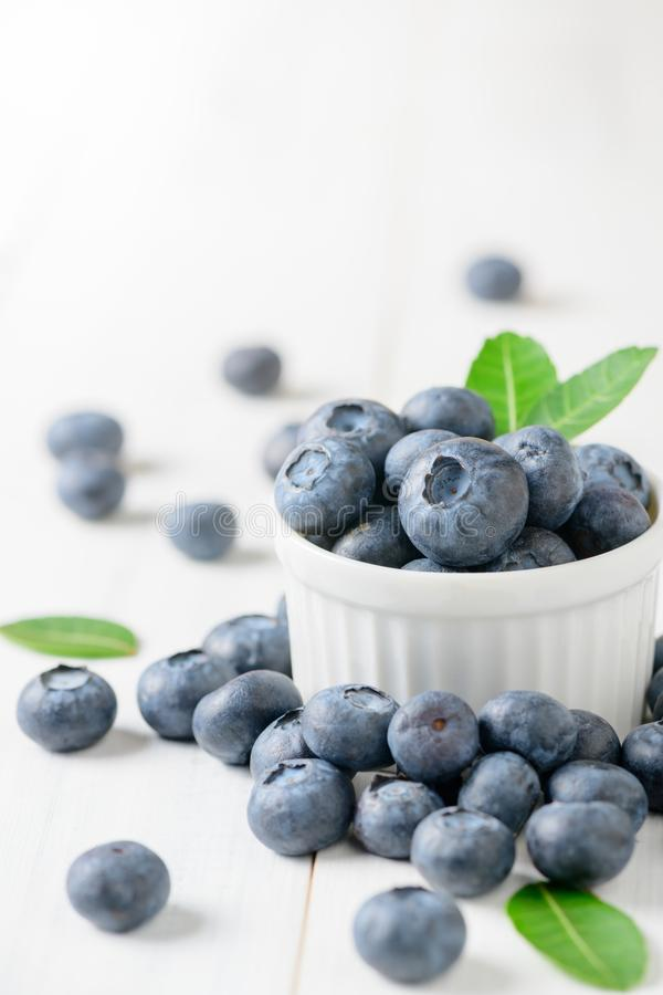 Fresh blueberry fruits with leaf on white glass royalty free stock images