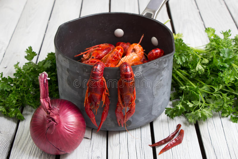 Fresh boiled crawfish with onion and parsley on the white wooden background. Rustic style. Fresh seafood. Steamed crayfish. Red boiled crawfish with onion and stock photo