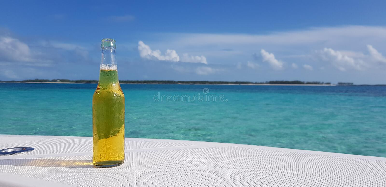 Fresh bottle of beer with the Caribbean Sea as background stock photography