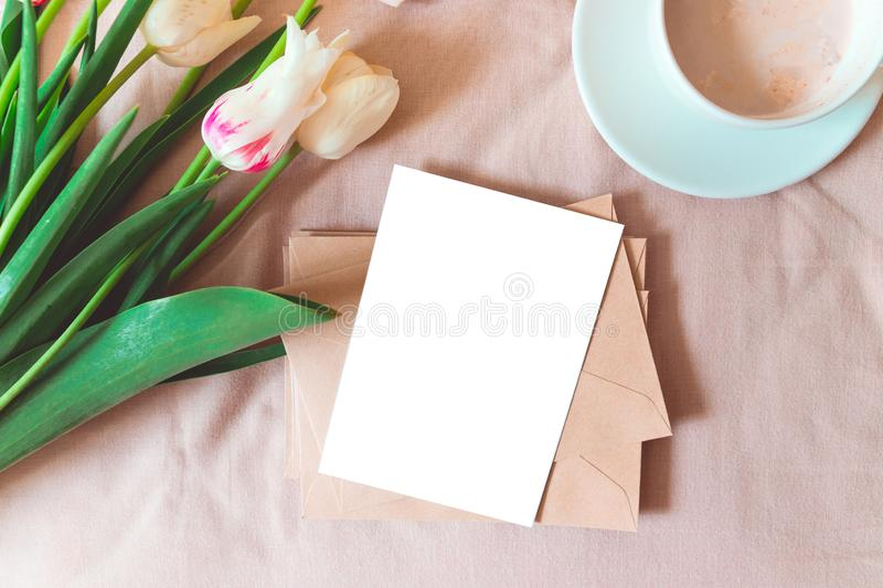 Good morning concept. Fresh bouquet of tulips, a cup of coffee kraft craft envelope with mockup postcard on clean white bedding. Good morning concept royalty free stock photo