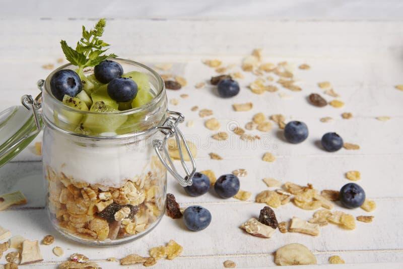 Fresh breackfast with cereals yogurt blueberry and kiwi royalty free stock photo