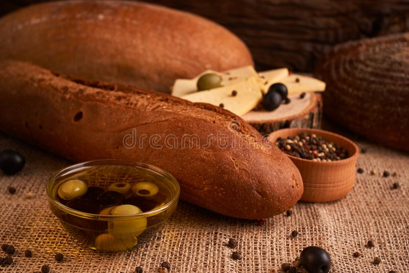 fresh bread baguette with olive oil, olives. cheese and rosemary on wooden background. Teasty breakfast stock photo