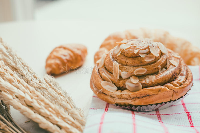 Fresh bread and baked goods on wooden. Chopping board, rustic style royalty free stock images