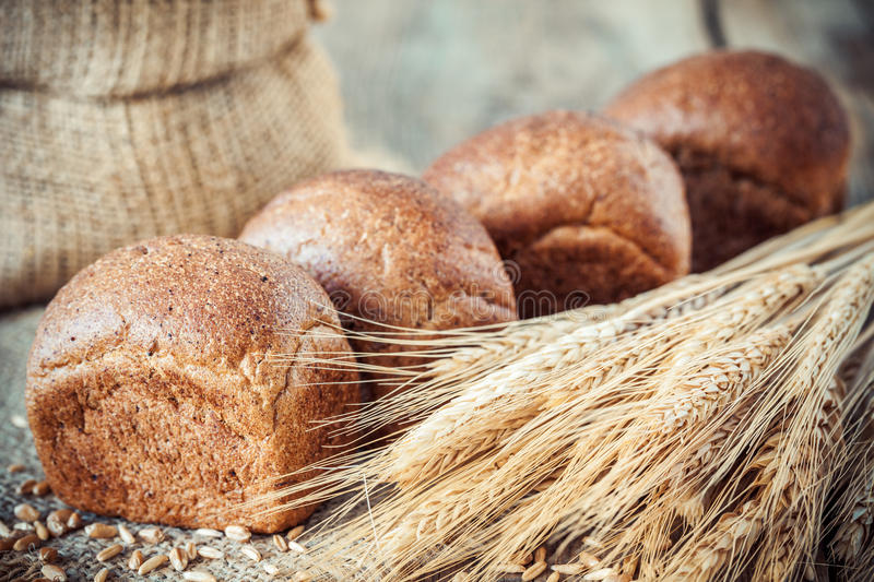 Fresh bread buns, wheat ears and sack of flour. royalty free stock photography
