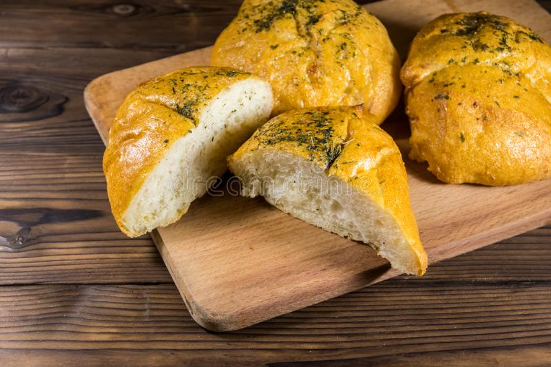 Fresh bread ciabatta on cutting board on wooden table royalty free stock photo