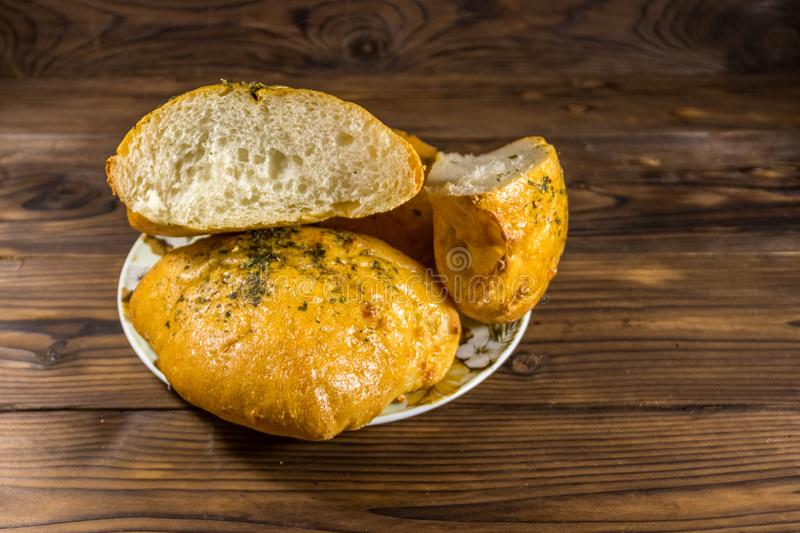 Fresh bread ciabatta on a plate on wooden table stock photography