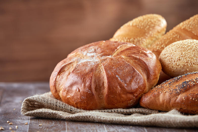 Fresh bread on a cloth linen with brown background on the wooden table with flour stock images