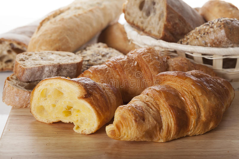 Fresh bread and croissants. Close up of fresh bread and french croissants on wooden board stock image