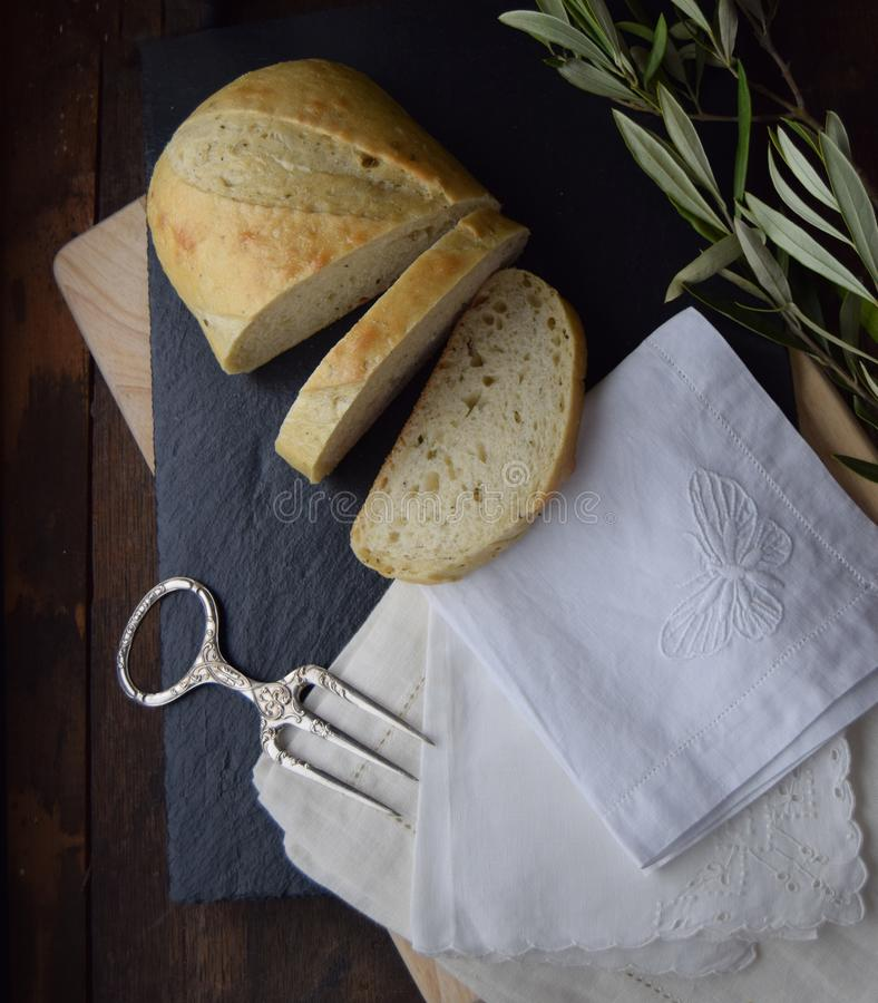Fresh Bread on Rustic Table and Linen Napkins. Fresh Bread with on dark slate chopping board on rustic European table. Dark wood background. Antique fork with royalty free stock image