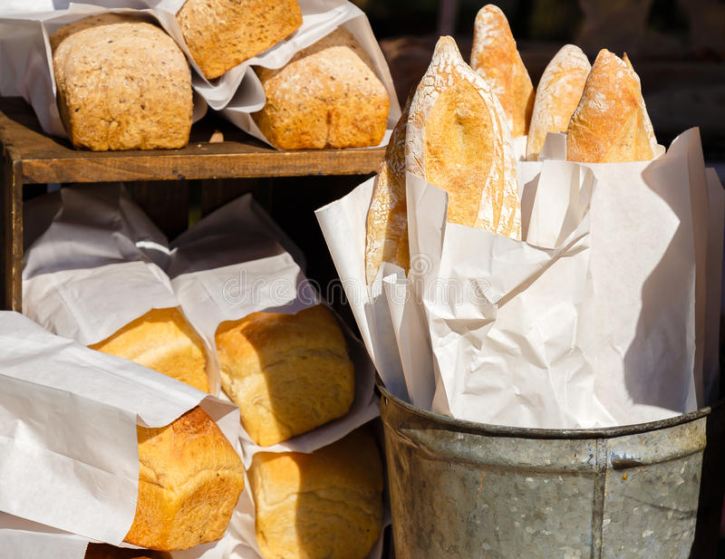 Fresh Bread in Paper. Freshly baked loaves of bread on display at a farmers market in Vermont, selling home made bread in white paper bags in a metal pail bucket royalty free stock image