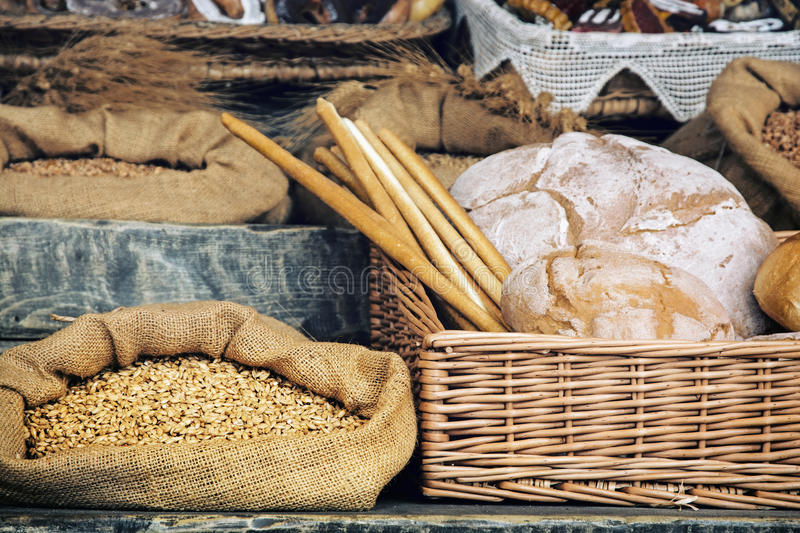 Fresh bread with pastry in the wicker basket and grain in the ba stock photos