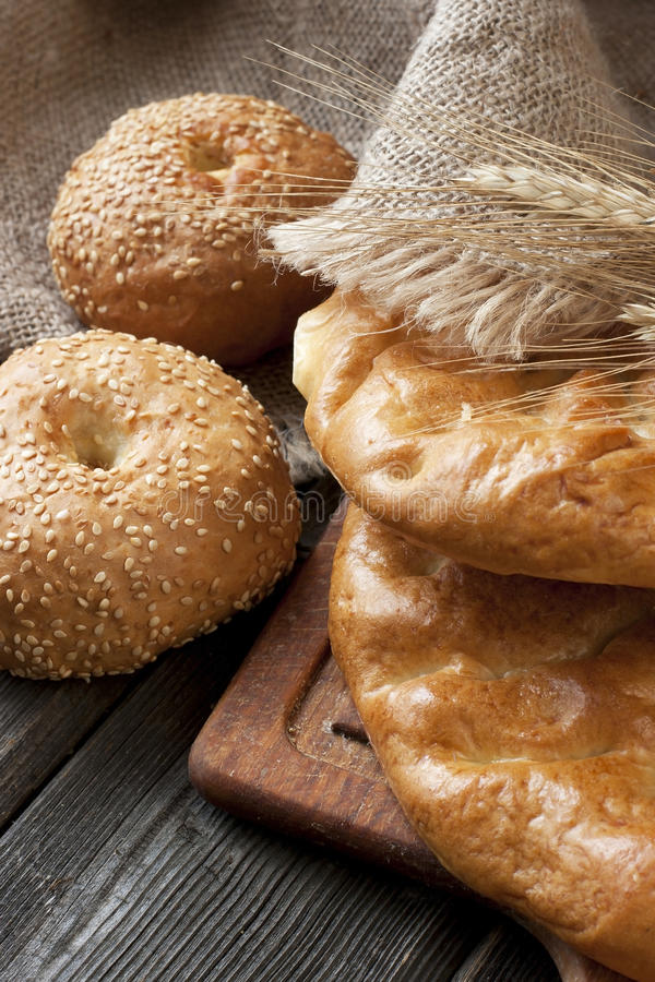 Fresh bread and rolls with ears of wheat on the wooden table royalty free stock photography