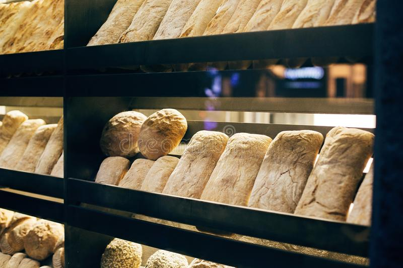 Fresh bread on shelves stand of a shop or bakery. Freshly baked bread loaves at window of store front. Organic pastry. Space for. Text stock photography