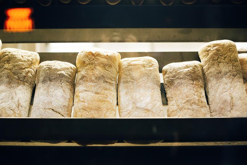 Fresh bread on shelves stand of a shop or bakery. Freshly baked bread loaves at window of store front. Organic pastry. Space for. Text royalty free stock photo