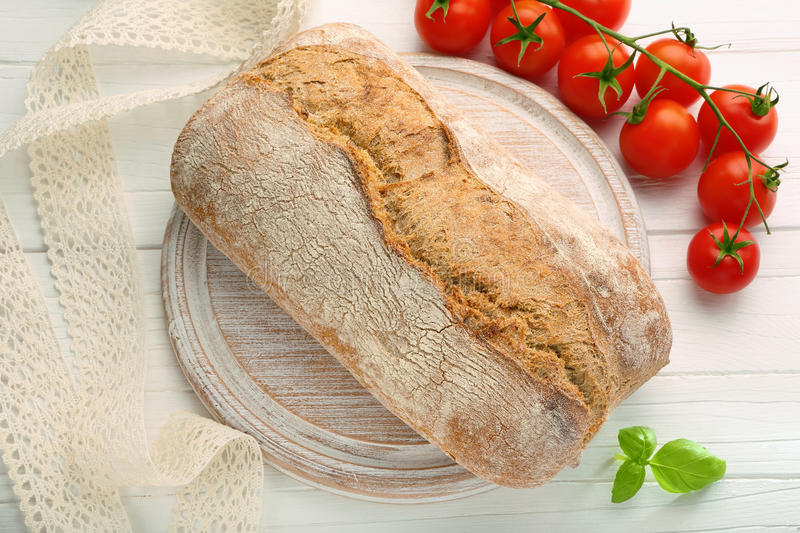 Fresh bread on a wooden board and tomatoes stock image