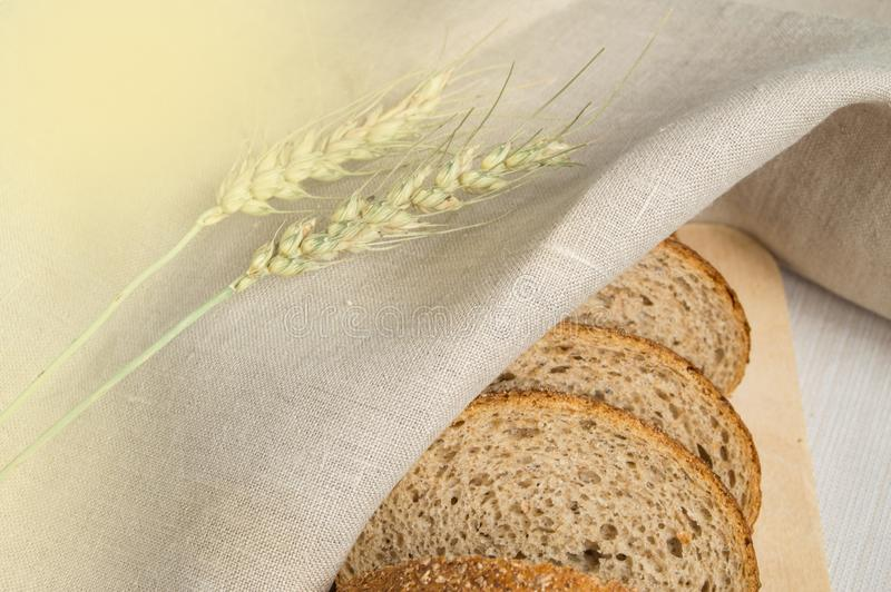 Fresh bread on a wooden chopping Board, wrapped in linen cloth, next to wheat ears, copy space, top view. Brown whole grain sliced royalty free stock images