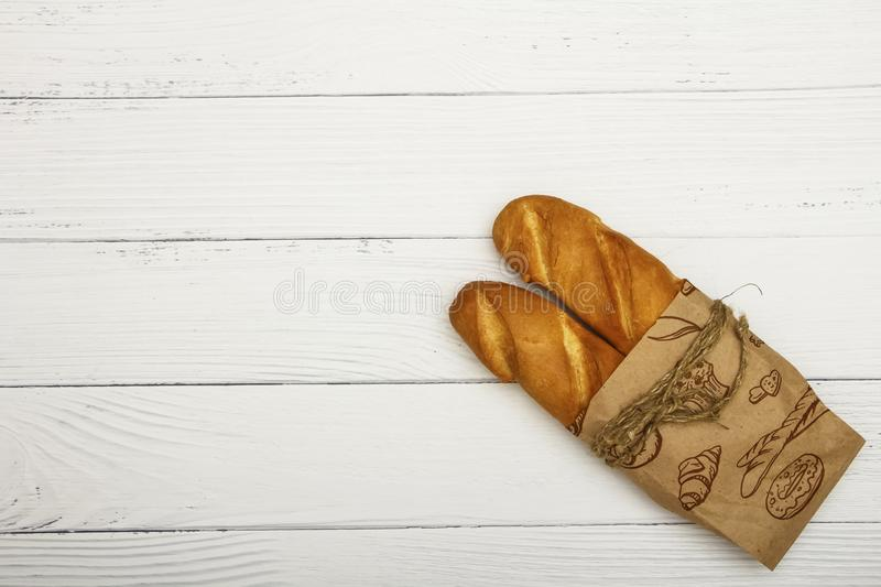 Fresh bread wrapped in old newspaper on a white wooden table. Top view with space for your text. stock photos