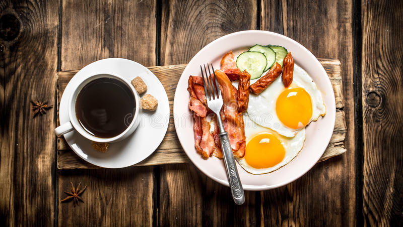 Fresh Breakfast. Cup of coffee , fried bacon with eggs. And smoked sausage. On wooden background royalty free stock photography