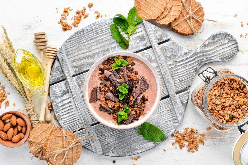 Fresh breakfast with yogurt, granola, chocolate and berries in a bowl. Top view. Free space for your text royalty free stock photography