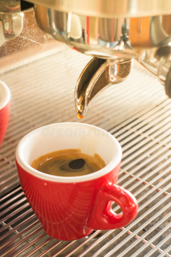 Fresh brew hot coffee from espresso machine with vintage filter royalty free stock image