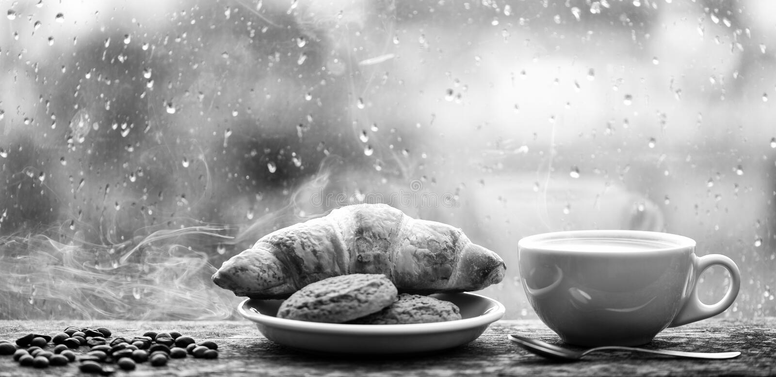 Fresh brewed coffee in white cup or mug on windowsill. Coffee drink with croissant dessert. Enjoying coffee on rainy day stock image